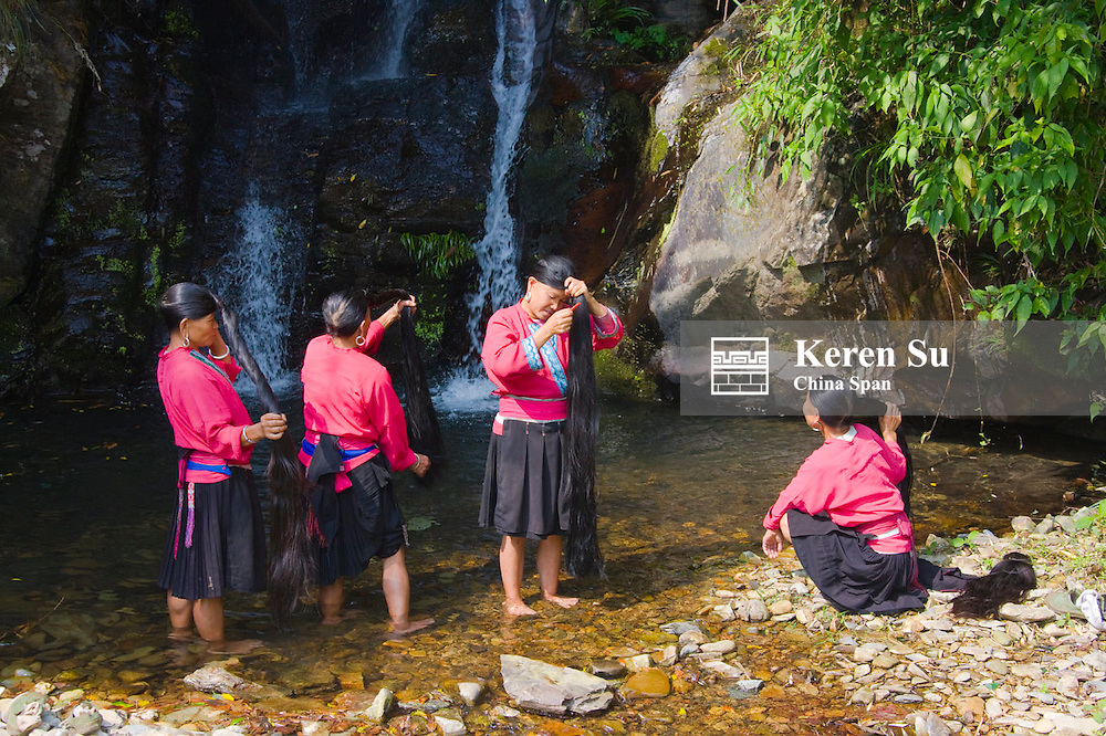 Red Yao girls brushing long hair by the waterfall,  Longsheng, Guangxi, China
