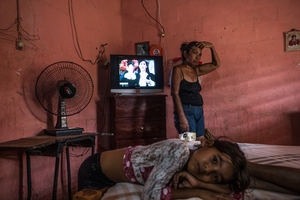 "LA VELA, VENEZUELA - SEPTEMBER 11, 2016: Minerba Piñero takes care of her elderly mother, Felipa Palencia de Piñero, who is diabetic, while her granddaughter, Karla Karina Piñero, 8, rests on the bed. Minerba also takes care of Karla, because her parents are working in Curacao. The family struggles to find the medicine that Felipa needs. To escape the crisis, Ms. Piñero's sister Maria spent all of her savings to pay smugglers to take her in a small fishing boat to Curacao island. ""I'm nervous,"" she said. ""I'm leaving with nothing. But I have to do this. Otherwise, we will just die here hungry."" Another benefit of living and working in Curacao, she said, is that she will be able to find and pay for her mother's medicines, and ship them to her in Venezuela.  Despite having the largest known oil reserves in the world, Venezuela is suffering from hyperinflation and a severe economic crisis making affordable food difficult for most middle and working class families to access.  Well over 150,000 Venezuelans have fled the country in the last year alone, the highest in more than a decade, according to scholars studying the exodus. As Hugo Chávez's Socialist-inspired revolution collapses into economic ruin, as food and medicine slip further out of reach, the new migrants include the same impoverished people that Venezuela's policies were supposed to help. ""We have seen a great acceleration,"" said Tomás Paez, a professor who studies immigration at the Central University of Venezuela. He says that as many as 200,000 Venezuelans have left in the last year, driven by how much harder it is to get food, work and medicine — not to mention the crime such scarcities have fueled.  PHOTO: Meridith Kohut for The New York Times"
