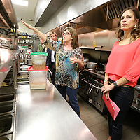 Park Heights owner Blair Hughes, center, shows the celebrity chefs like Lori Bevering, right, and others their stations during a tour of the kitchen as they get ready for this year's annual Cooking Like the Stars fund raiser for the North Mississippi Boys & Girls Club.