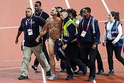 London, 2017 August 05. A streaker with 'Peace + Love' written on his chest is detained and escorted from the track at the IAAF World Championships London 2017. © Paul Davey.