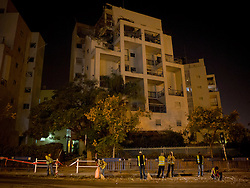 © Licensed to London News Pictures 20/11/2012.  Rishon Lezion, Israel.  Local workers clean up the damage to an apartment building which was hit by a rocket.  The city, which sits below Tel Aviv has never been hit before.  The rocket ? said to be carrying 90 kilograms of explosives ? penetrated through three floors of the building, causing extensive damage, but no serious injuries as all of the residents were in their safe rooms.  Photo credit : Alison Baskerville/LNP