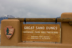 Welcome sign to Great Sand Dunes National Park and Preserve with snow capped Sangre de Christo mountains in the background. Great Sand Dunes National Park and Preserve contains the tallest sand dunes in North America. The Dunefield, topping off with Star Dune at 750 feet, is created by sand trapped by the nearby Sangre de Christo Mountains (larger rougher grains and pebbles) and the San Juan Mountains (65 miles to the west).  Waterways such as Medano Creek help carry the sediment down to the San Luis valley where the dunes are found. Great Sand Dunes National Park and Preserve, Mosca, Colorado.