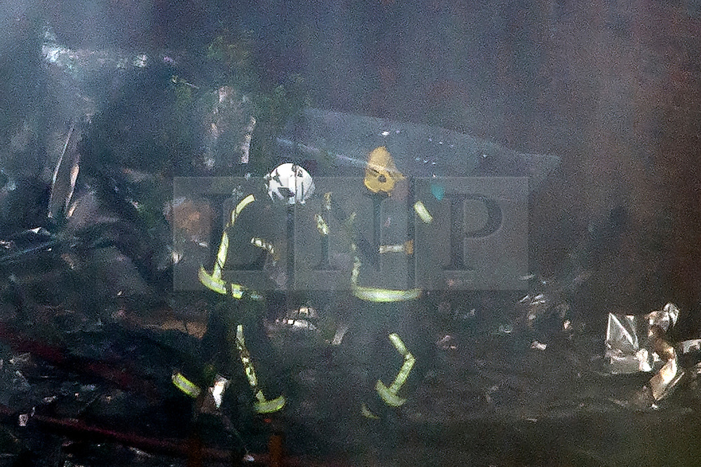 © Licensed to London News Pictures. 14/06/2017. London, UK. Firemen use shields to protect themselves from falling debris as they enter the tower block, at the scene of a huge fire at Grenfell tower block in White City, London. The blaze engulfed the 27-storey building with 200 firefighters attending the scene. There were reports of people trapped in the building. Photo credit: Ben Cawthra/LNP