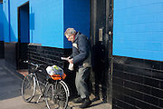 An elerly man reads his local newspaper standing in a blue walled doorway near his pedal bike.