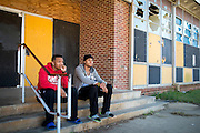 "Kyle Simon and Jessie Cole hang out on the steps of the Grambling State University Natatorium in Grambling, Louisiana on October 23, 2013. The natatorium is boarded up with most windows broken out but plans to renovate the building into a new Health and Wellness Center are ""coming soon.""   (Cooper Neill for The New York Times)"