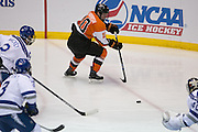 RIT defenseman Brady Norrish skates the puck behind the Air Force net during the Atlantic Hockey semifinal at the Blue Cross Arena at the War Memorial in Rochester on Friday, March 18, 2016.