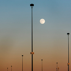 A nearly full moon rises over lights in a parking lot off of Fairpark lane in Boise, Idaho. July's full moon in Boise will be at 12:16pm. Sunday July 21, 2013