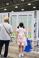 Två AKB48-fans letar upp sina idoler i de stora mässhallarna. Tusentals fans har kommit till Makuhari Messe i Chiba City för att få möjlighet att skaka hand med sin favoritmedlem i popgruppen AKB48.