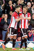 Brentford striker, Scott Hogan (9) celebrating with Brentford midfielder, Konstantin Kerschbaumer (17) after scoring his second goal of game 3-0 during the Sky Bet Championship match between Brentford and Fulham at Griffin Park, London, England on 30 April 2016. Photo by Matthew Redman.