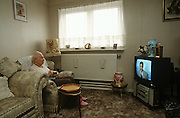 An elderly lady resident of a tower block, enjoys the company of TV newsreader in her inner-city home.