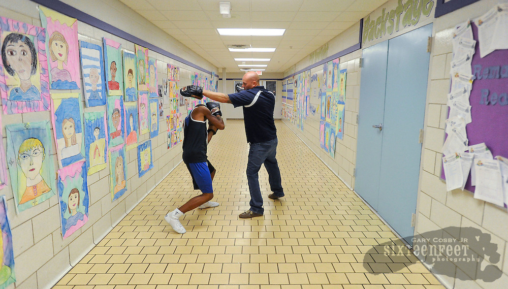 Daily Photo by Gary Cosby Jr.    ..Derek Moon, right, trains fighter Austin Teagues in a hallway at Leon Sheffield Elementary during a night of boxing at Leon Sheffield hosted by Decatur Youth Services.........................