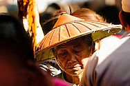 an old woman walking in a crowd in inle lake market, myanmar