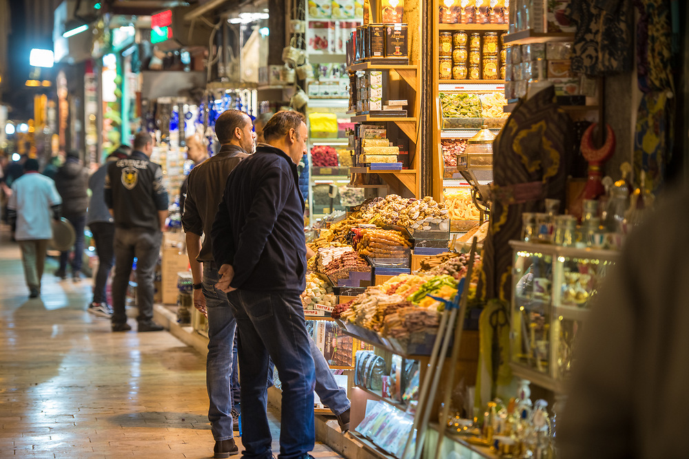 Men stand at front of storefront off of main avenue of  Istanbul Spice bazaar in Turkey and browse through the goods they are selling