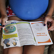 Kimberly Torres, 21, looks at materials explaining the Zika virus and how to protect yourself against the virus, at her home near Guayama, Puerto Rico. Stephanie is pregnant with her second child. Right now, Zika is spreading rapidly in Puerto Rico and pregnant women are at risk for becoming infected with Zika which can cause microcephaly and other birth defects. If the current trends continue, at least 1 in 4 people, including women who become pregnant, may become infected with Zika.