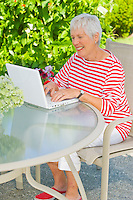Mature woman working outside on a patio table with her laptop computer