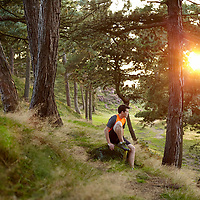 A photograph of a runner taking a break in the woods while the sun sets on Ilkley Moor, Yorkshire, England