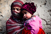 Afghanistan: A young mother and her daughter at her makeshift home at Tamil Mill Bus site in Kabul city. ..Afghans returning from exile abroad face many challenges. Security is a major obstacle to return in many districts. Others choose not to return tot heir villages because of landlessness or the lack of job opportunities, fuelling population movements and especially further urbanisation. Impoverished returnees and IDP's living in Kabul cit struggle to meet their daily needs. The attraction of daily wage labour draws growing numbers tot he city. But the rising cost of rental accommodation and basic commodities price them out of the market and relegate them to life in the informal settlements which have mushroomed across the city...While 70-80% of kabul city os considered as 'informal' in the sense it is not covered by the Kabul Master Plan, UNHCR's focus is on a limited number of highly documented such 30 sites dotting the city which are home to over 2,000 families. Some families are living under canvas and the constant threat of eviction. others have gained a toe-hold in abandoned around building in the city...Afghanistan/UNHCR/Jason Tanner/February 2011