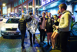 © Licensed to London News Pictures . 01/01/2018. Manchester, UK. A man wrapped in a silver heatproof blanket is helped by another outside the Birdcage on Withy Grove . Revellers celebrate the start of the New Year in Manchester City Centre . Photo credit: Joel Goodman/LNP
