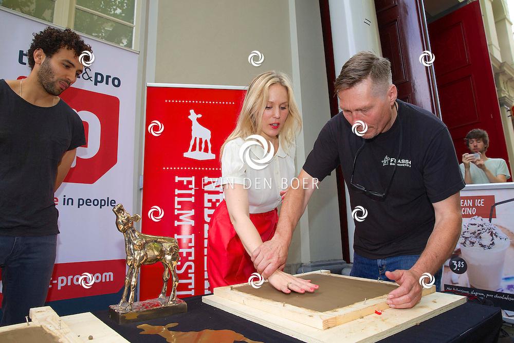 UTRECHT - Het maken van de Gouden Tegel-handafdrukken van Gouden Kalf-winnaars Marwan Kenzari (WOLF) en Hadewych Minis (BORGMAN) op de Talent & Pro Filmboulevard. Met hier op de foto gieter Jos Stijlaart die Marwan Kenzari en Hadewych Minis een handje helpt. FOTO LEVIN DEN BOER - PERSFOTO.NU