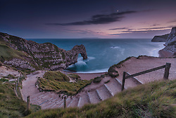 The moon over Durdle Door on the Jurassic Coast in Dorset at sunset.