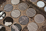 Aerial of Solar Facility in Borrego Springs, California uses both photovoltaic and solar thermal systems. What makes their operation unique is that they use 3 acre round ponds to float their solar arrays on. The ponds act as a water bearing tk (frictionless) so that it requires very little energy to have the whole surface of the pond rotate to face the sun as it moves east to west. A series of small motors tilt the individual rows of the arrays to track the sun vertically as well. They use hot water from one type of array to run a huge still, which produces alcohol from molasses. So far there are 18 ponds. (1985).