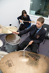 Secondary school students playing musical instruments in a music lesson,