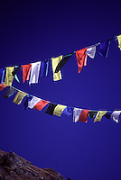 Brightly coloured prayer flags colour the blue sky above Khumjung in the high Himalayas of Nepal.