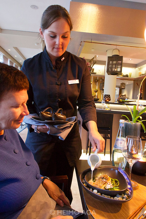 Sylt, Germany. List. Spa Resort A-Rosa Sylt. Spices Restaurant.<br /> STEAMBOAT, Wolfsbarsch, Wasserspinat, Baby-Krake, Pilze<br />Gemüse, Kondensmilch.