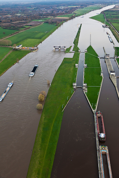 Nederland, Noord-Brabant, Sambeek, 15-11-2010;  Het sluis en stuwcomplex Sambeek bij hoogwater van de Maas. Het hoogwater Maas is een gevolg van sneeuwsmelt en neerslag in de bovenloop van de rivier. De stuw is gestreken en de scheepvaart kan gebruik maken van de vaargeul naast de stuwtorens. De schutsluizen staan geheel onder water, de bedieningsgebouwen staan op kolommen boven het water. Het complex is gebouwd in het kader van de kanalisatie van de Maas in de jaren 1918 - 1929. Lock and weir complex Sambeek at high waters of river Meuse. The flood is due to snow melt and precipitation upstream. The weir is 'lifted' allowing for ships to pass. The normal shipping locks lock are completed flooded (and under water). The control buildings are build on columns. The whole complex was built in the context of the canalization of the Meuse in the years 1918 to 1929. luchtfoto (toeslag), aerial photo (additional fee required) © foto/photo Siebe Swart