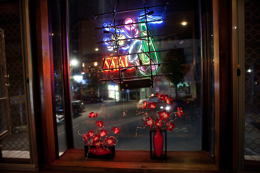 The bar window decorated with flowers and neon lights, evening view to the street / Uljin, South Korea, Republic of Korea, KOR, 04 October 2009.
