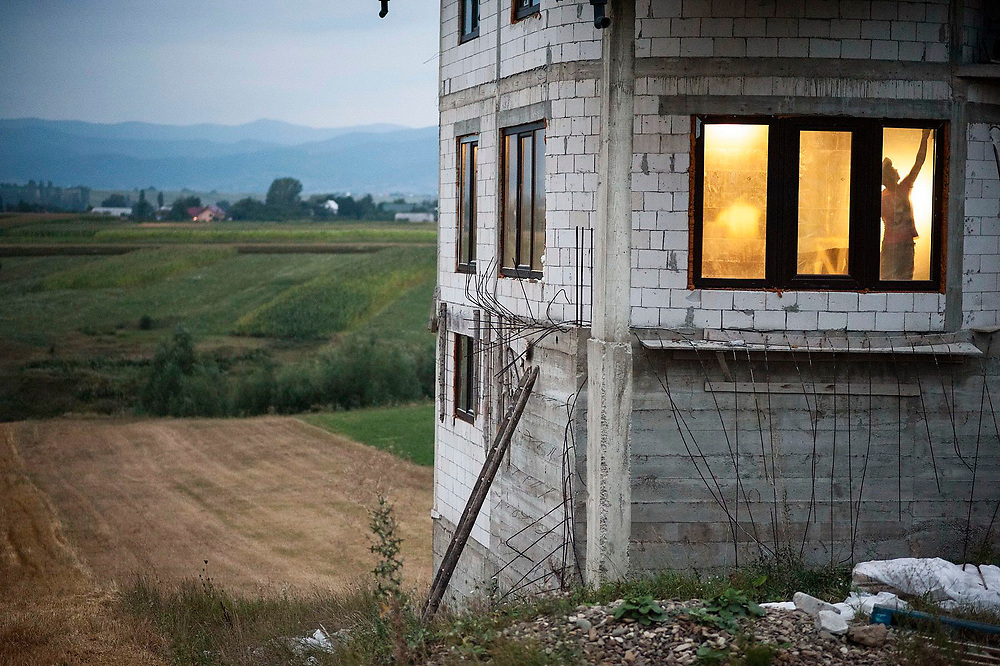 A man works on his new house in the village of Cajvana. Many people in the village have made money abroad, mainly working in the construction industry, and are building large new homes when they come back to Romania.