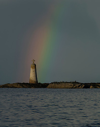 A rainbow over St Baldred's Cross at Seacliffe Beach near to North Berwick in East Lothian