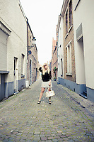 A young woman posing in an alley in Brugge