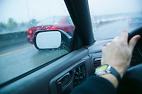 Drivers arm and view through windows on a highway in the rain.