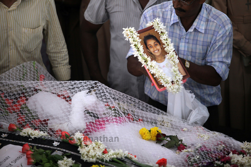 A relative places a photo of H.Gloria, an Air India Express crash victim over her coffin during her funeral service  at the St. Alphonsa Catholic Church, on May 23, 2010 in Mangalore. H.Rosaline and her two daughters H.Goldine and H.Gloria were passengers of the Air India Express Boeing 737-800 series aircraft arriving from Dubai, with 166 people onboard. Th flight overshot the runway on landing in Mangalore and crashed into a forest. Airline officials say 8 survivors have been rescued with 158 others feared dead. (Photo by Prashanth Vishwanathan/Getty Images)