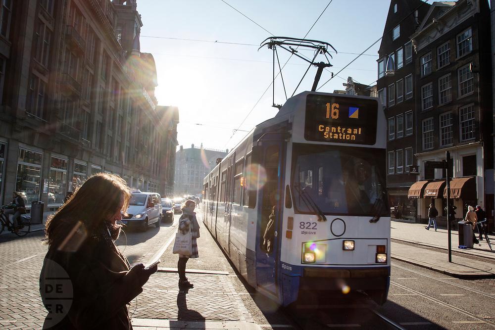 In Amsterdam wachten voetgangers op het Damrak met oversteken voor de tram voorbij is gereden. Het Damrak is onlangs opnieuw ingericht met een duidelijkere scheiding tussen fietsers, trams en auto's.<br /> <br /> In Amsterdam pedestrians wait for the tram to cross the Damrak. The Damrak is newly redesigned with a clearer separation between cyclists, trams and cars.