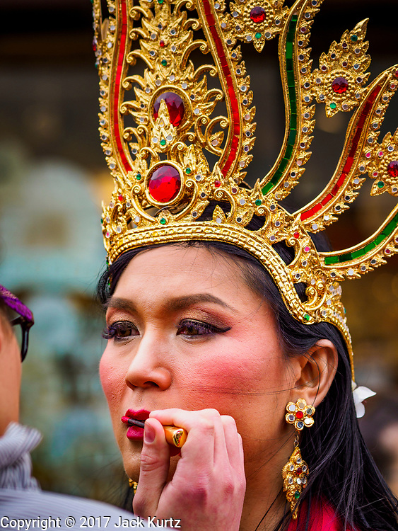 """29 APRIL 2017 - MINNEAPOLIS, MINNESOTA: A performer gets her makeup put on before going on stage at the Songkran Uptown festival. Several thousand people attended Songkran Uptown on Hennepin Ave in Minneapolis for the city's first celebration of Songkran, the traditional Thai New Year. Events included a Thai parade, a performance of the Ramakien (the Thai version of the Indian Ramayana), a """"Ladyboy"""" (drag queen) show, and Thai street food.     PHOTO BY JACK KURTZ"""