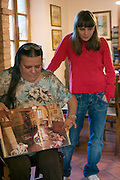 ITA.MWdrv05.169.xrw..Daniela Ciolfi shows a picture of her daughter Caterina as a young girl made by the photographer Catherine Karnow, who photographed the Pellegrini family for the book Women in the Material World (1995). Revisit with the Pellegrini family, 2005, Pienza, Italy. The Pellegrinis were also Italy's participants in Material World: A Global Family Portrait, 1994 (pages: 198-199), for which they took all of their possessions out of their house for a family-and-possessions-portrait. In 1996, UNESCO declared the town a World Heritage Site...