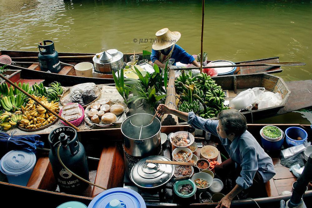 Damnoensaduak Floating Market, sloe view of one restaurant boat filled with soup ingredients.