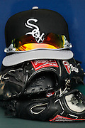 A Chicago White Sox hat and gloves are stacked up in the White Sox dugout before a baseball game against the Kansas City Royals at Kauffman Stadium in Kansas City, Mo., Sunday, May 5, 2013.  (AP Photo/Colin E. Braley).