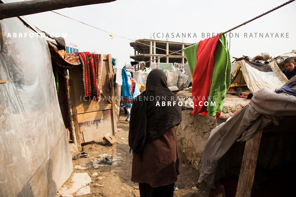 A women walking through a small alley of of tent houses in a refugee camp in Kabul