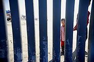 A Honduran child looks through the U.S.-Mexico border fence at Borderfield State Park in San Ysidro, California on Tuesday, November 20, 2018.