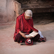 Buddhist woman reading in Boudhanath stupa a World Heritage site and one of the most important place of Buddhist pilgramagre located in the outskirts of Kathmandu, Nepal