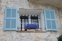 A window with blue shutters and purple flowers in St. Paul-de-Vence.