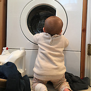 A nine month old baby girl watching the washing machine.  Photo Tim Clayton