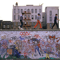 Kids walk along the top of a grafitti-covered wall in Manhattan;s Lower East Side in the 1980s.