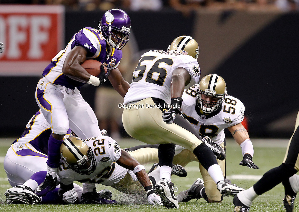 September 9, 2010; New Orleans, LA, USA; Minnesota Vikings running back Adrian Peterson (28) is pursued by New Orleans Saints cornerback Tracy Porter (22), linebacker Jo-Lonn Dunbar (56) and linebacker Scott Shanle (58) during the NFL Kickoff season opener at the Louisiana Superdome. The New Orleans Saints defeated the Minnesota Vikings 14-9.  Mandatory Credit: Derick E. Hingle