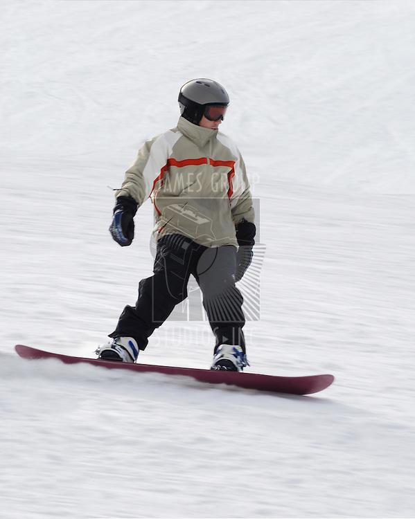 A Man Snowboarding fast down a hill.