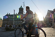 In Amsterdam steekt de man op de fiets de Dam over.<br /> <br /> In Amsterdam a man is crossing the Dam on his bike.