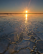 The sun rises over Emiquon National Wildlife Refuge on a frigid winter morning. Since the water froze rapidly the day before, it created interesting patterns in the ice. Despite the subzero windchill, numerous wildlife were out on this morning. On the other side of the lake coyotes, bald eagles, geese, and other birds could be seen.<br />